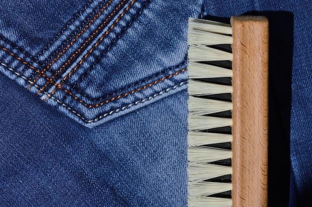 Une brosse à vêtements se trouve sur un jean plié