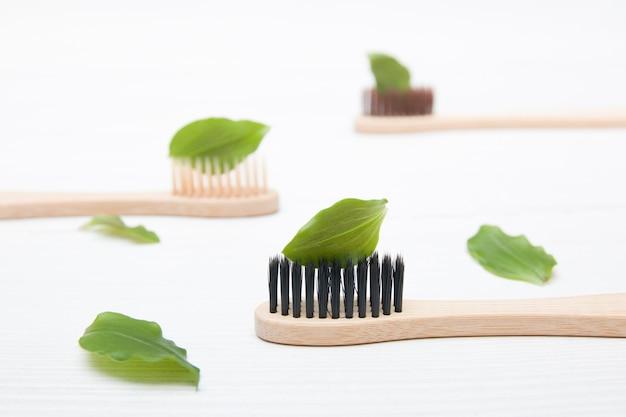Brosses en bambou avec moulures sur fond clair, une feuille sur la brosse comme du dentifrice, concept zéro déchet, cosmétiques naturels