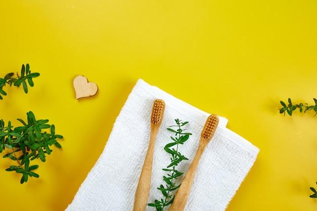 Brosses à dents en bambou et bâtonnets d'oreille feuilles vertes sur papier jaune