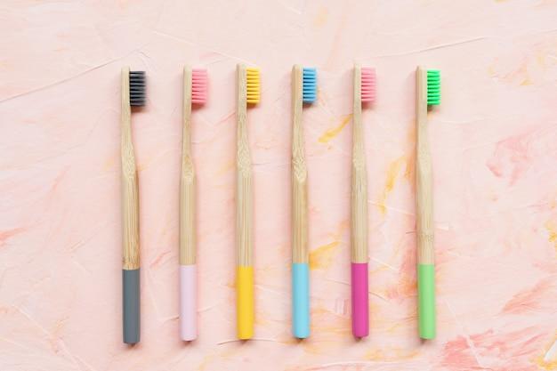 Brosses à dents en bambou en bois naturel sur surface rose