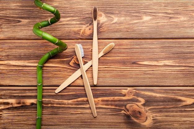 Brosses à dents en bambou, branche de bambou sur fond de bois. espace de copie à plat.