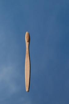 Les brosses à dents en bambou clair se reflètent dans le miroir contre le ciel bleu.
