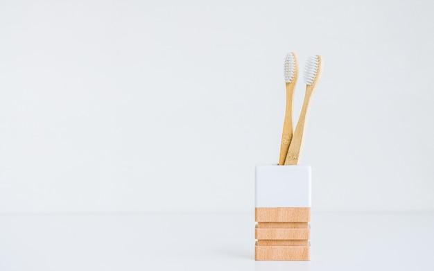 Brosses à dents en bambou dans une tasse en bois avec des matériaux naturels, isolées sur fond blanc avec espace de copie.