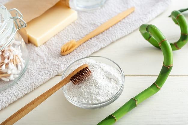 Brosses à dents en bambou, dentifrice en poudre sur blanc