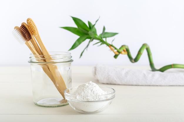 Brosses à dents en bambou, dentifrice en poudre sur fond blanc.