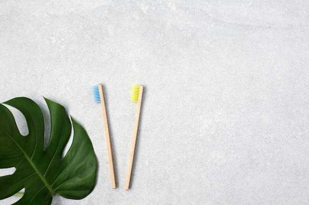 Brosses à dents en bambou et feuilles vertes sur table en pierre