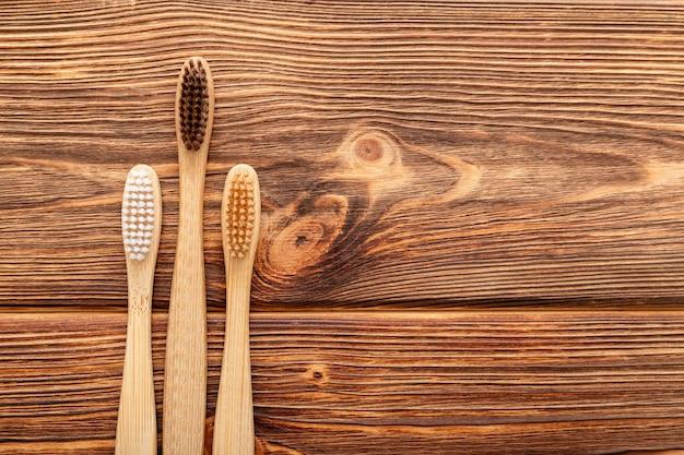 Brosses à dents en bambou sur fond de bois. mise à plat avec espace copie