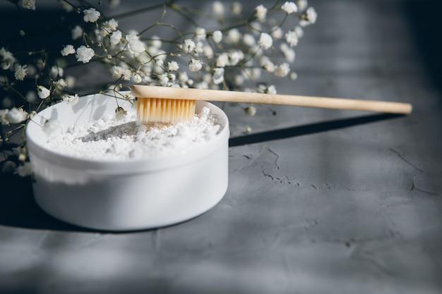 Brosses à dents en bambou naturel et poudre à dents sur une table grise
