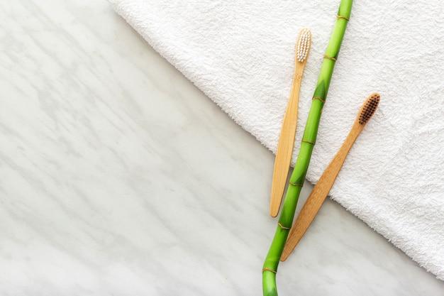 Brosses à dents en bambou, plante en bambou sur une serviette blanche, fond de marbre. mise à plat.