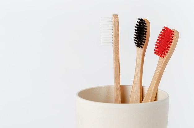 Brosses à dents en bambou rouge, blanc et noir en coupe écologique sur blanc