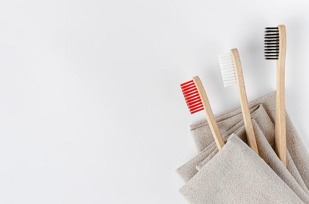 Brosses à dents en bambou sur une serviette en lin. mise à plat, espace copie.
