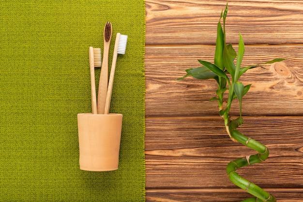 Brosses à dents en bambou en usine de bambou en verre d'argile sur fond de bois. mise à plat zéro déchet