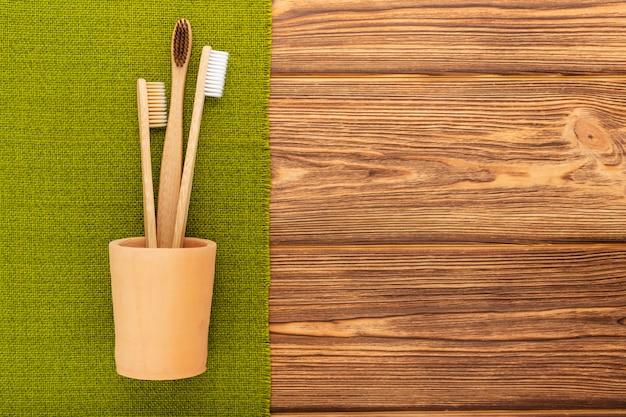Brosses à dents en bambou en verre d'argile avec une serviette verte sur bois