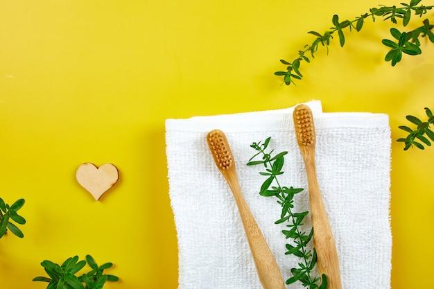 Brosses à dents et bâtons d'oreille en bambou, et feuilles vertes sur un mur de papier jaune, respectueux de l'environnement, produits d'hygiène personnelle zéro déchet, concept de soins dentaires