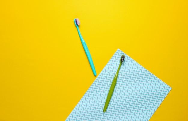 Brosses à dents bleues et vertes isolées sur jaune