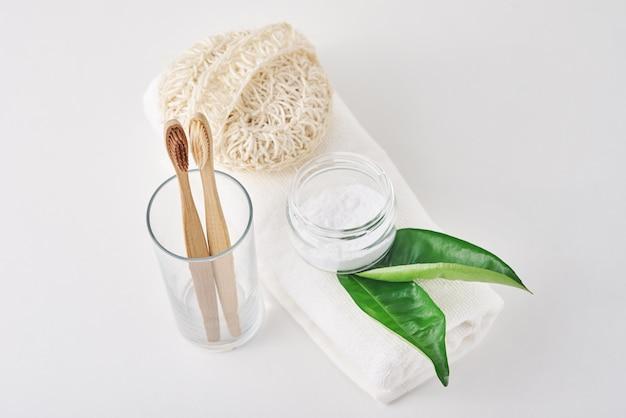 Brosses à dents en bois de bambou en verre, bicarbonate de soude et serviette sur fond blanc. concept d'hygiène personnelle