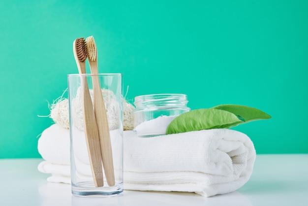 Brosses à dents en bois de bambou en verre, bicarbonate de soude et serviette sur un green. concept d'hygiène personnelle