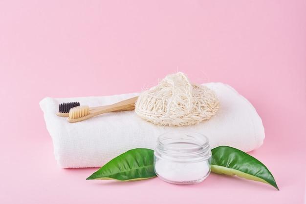 Brosses à dents en bois et bicarbonate de soude de bambou sur fond rose, concept de soins dentaires et d'hygiène