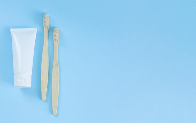 Brosses à dents en bois et dentifrice vue de dessus sur fond bleu