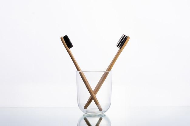 Brosses à dents écologiques en bois dans un verre en verre