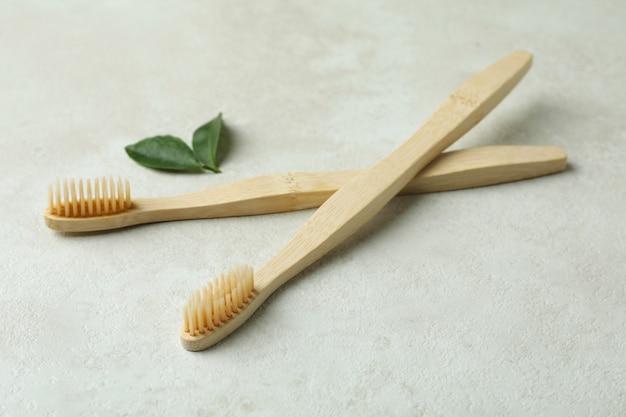 Brosses à dents écologiques et feuilles sur fond texturé blanc