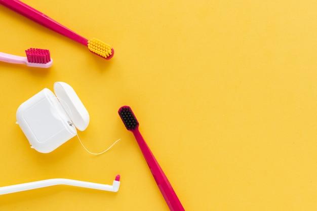 Brosses à dents hygiène dentaire, la soie dentaire à plat poser, vue de dessus, fond, jaune