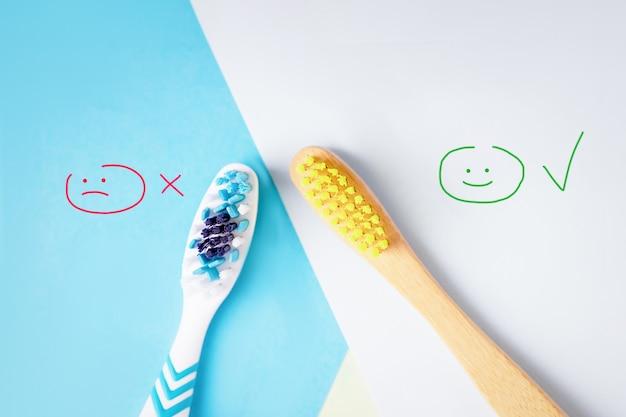 Brosses à dents en plastique et en bambou sur fond bleu et blanc, sélection de brosse à dents, écologique ou en plastique