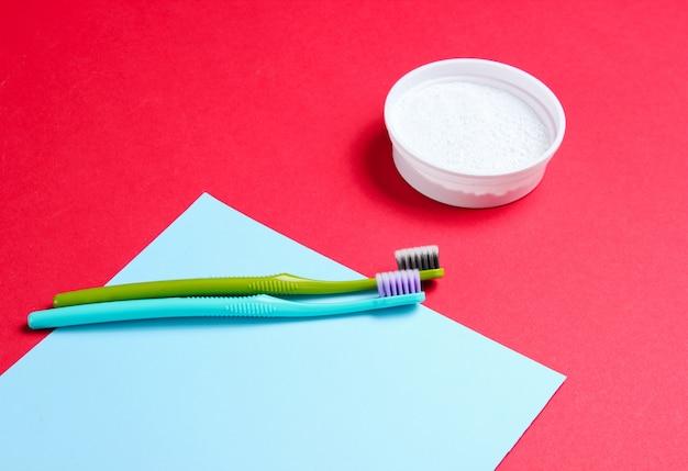 Brosses à dents et poudre à dents sur papier bleu rouge et