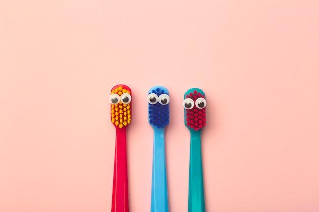Brosses à dents pour enfants de différentes couleurs sur rose