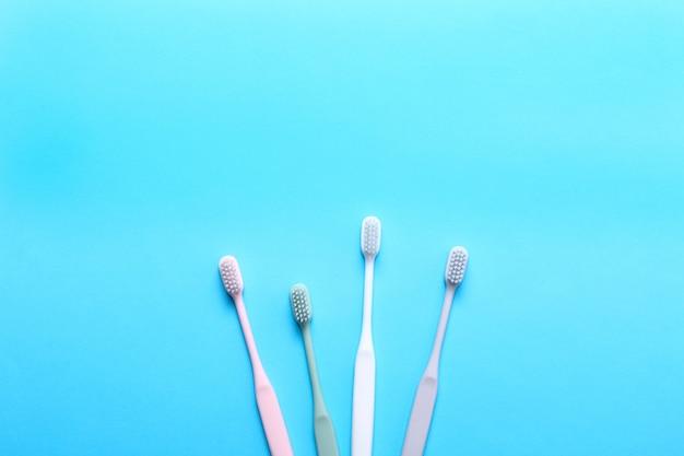 Brosses à dents roses, vertes, blanches et grises sur mur bleu.