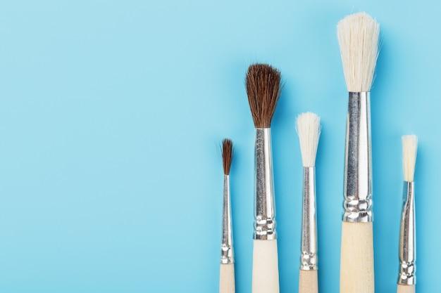 Brosses à dessin en bois naturel et laine. sur fond bleu.
