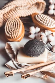 Brosses naturelles en bois et savon sur fond de béton, brosses à dents et brosses pour le corps en bambou, savon artisanal avec luffa, concept de mode de vie écologique et zéro déchet, espace copie