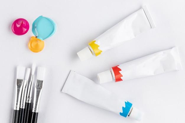 Brosses et tubes de peinture sur table blanche