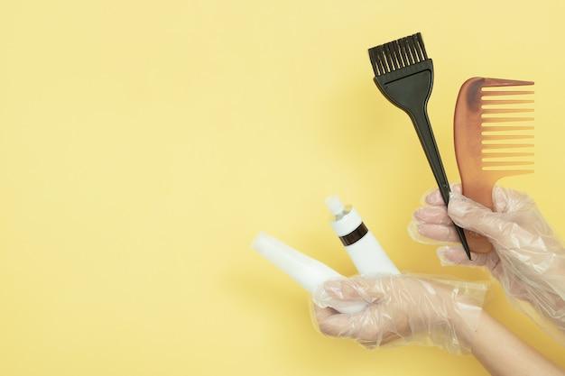 Brosses et tubes pour teindre les cheveux dans les mains gantées sur fond jaune avec espace de copie