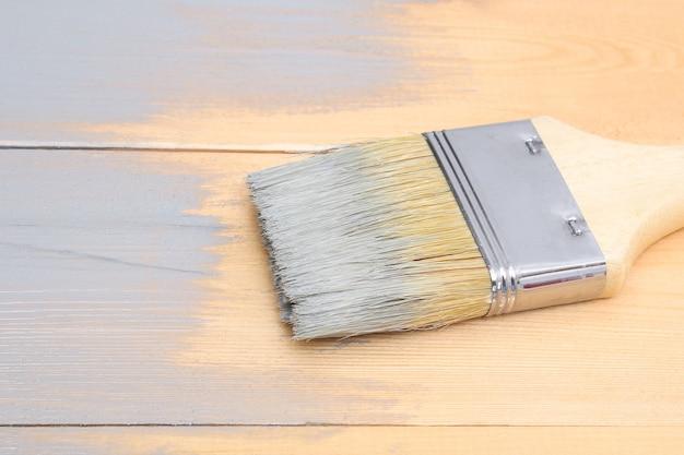 Brossez avec de la peinture à la main. l'homme peint des planches de bois dans un pinceau gris.