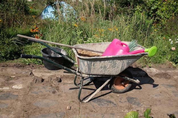 Une brouette de jardin remplie de sable et de mélange de ciment sec se dresse sur le chemin du jardin
