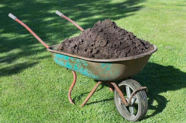 Brouette de jardin remplie de terre dans une ferme.