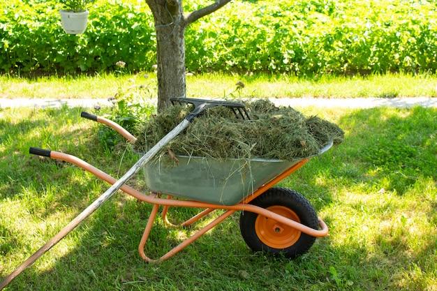 Une brouette de jardin se dresse dans l'arrière-cour d'une ferme. outils supplémentaires à proximité.