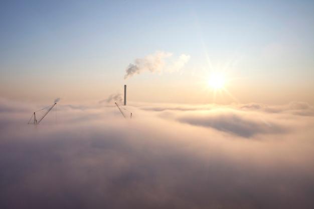 Brouillard épais sur la ville, aube ensoleillée pourpre sur les nuages, concept de pollution par la fumée atmosphérique