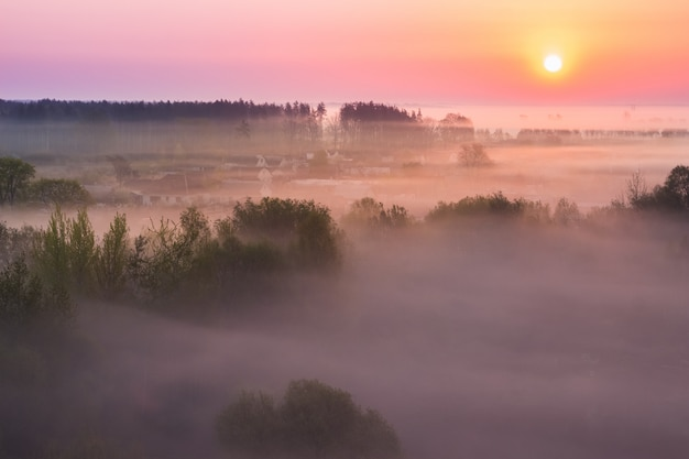 Brouillard printanier sur le village au lever du soleil