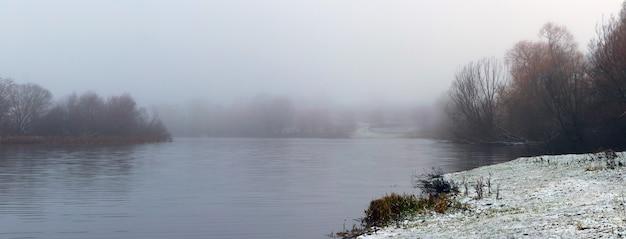 Brouillard sur la rivière et berge enneigée en hiver, arbres sur la berge