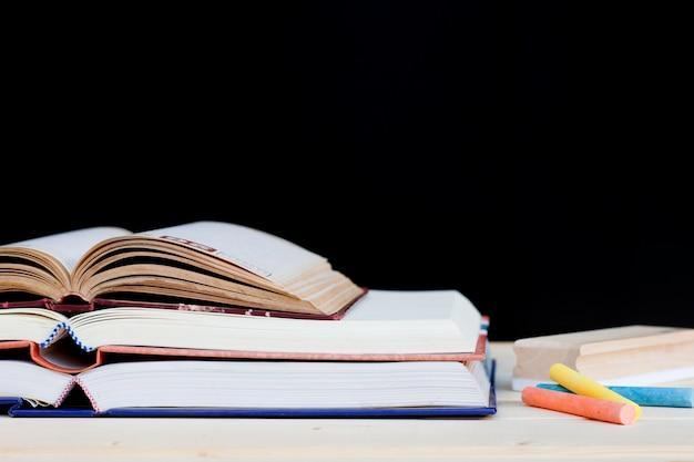 Brouillon, livres et craie sur fond de tableau