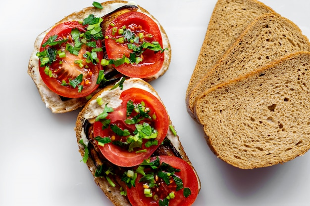 Brown fait griller des tranches de pain chaud avec des tomates en tranches rouges et des aubergines noires frites avec des verts sur le sol blanc