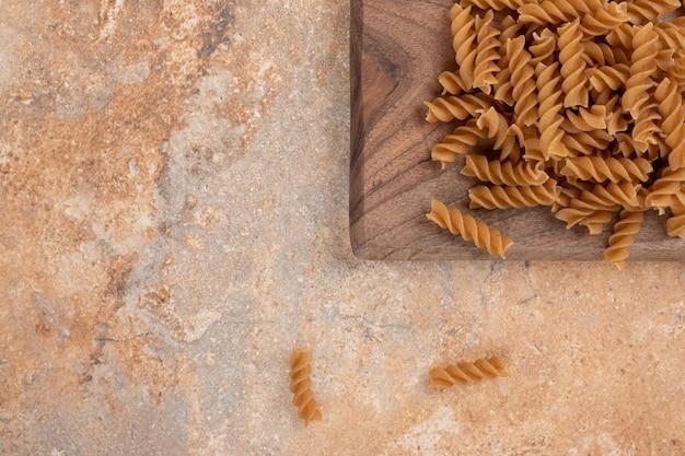 Brown macaronis en spirale non cuits sur planche de bois.