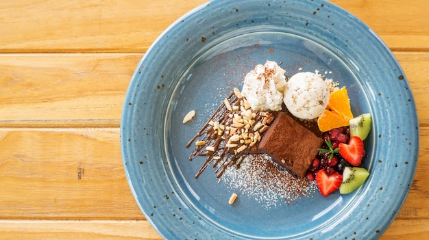 Brownie au chocolat avec crème glacée et mélanger les fruits dans une assiette bleue.