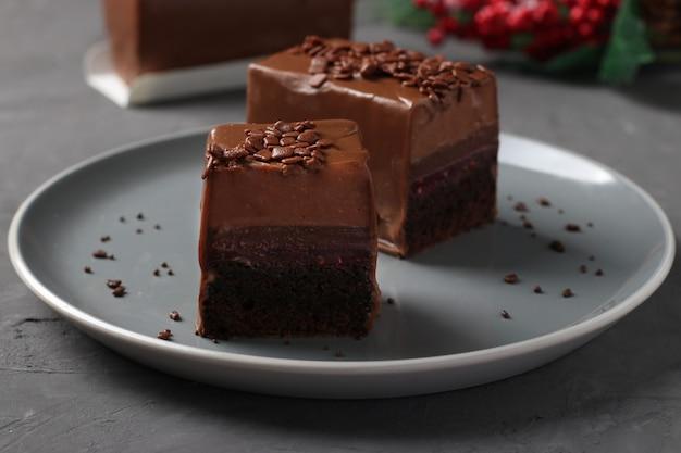Brownie au chocolat avec framboises confites et mousse au café recouvert de glaçage au chocolat gourmand sur fond gris foncé.