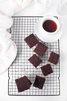 Brownie au chocolat et une tasse de thé sur la grille de support