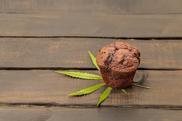 Brownie cupcake au chocolat avec feuille de chanvre sur fond en bois avec un espace pour le texte cuisine avec canna...