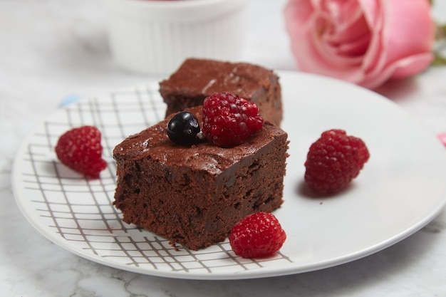 Brownie fudgy aux fruits rouges sur fond de marbre blanc.