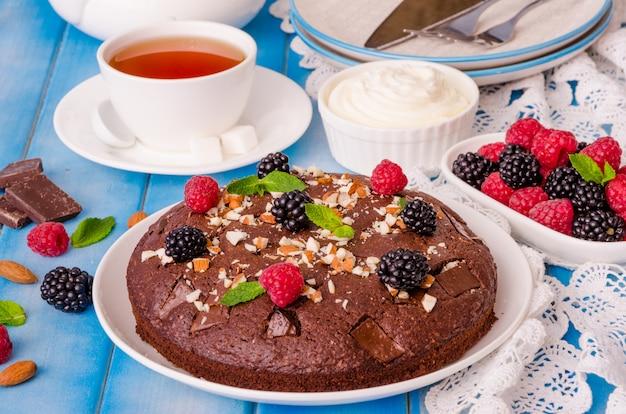 Brownie gâteau au chocolat avec framboises, mûres, amandes et crème fouettée sur fond en bois.